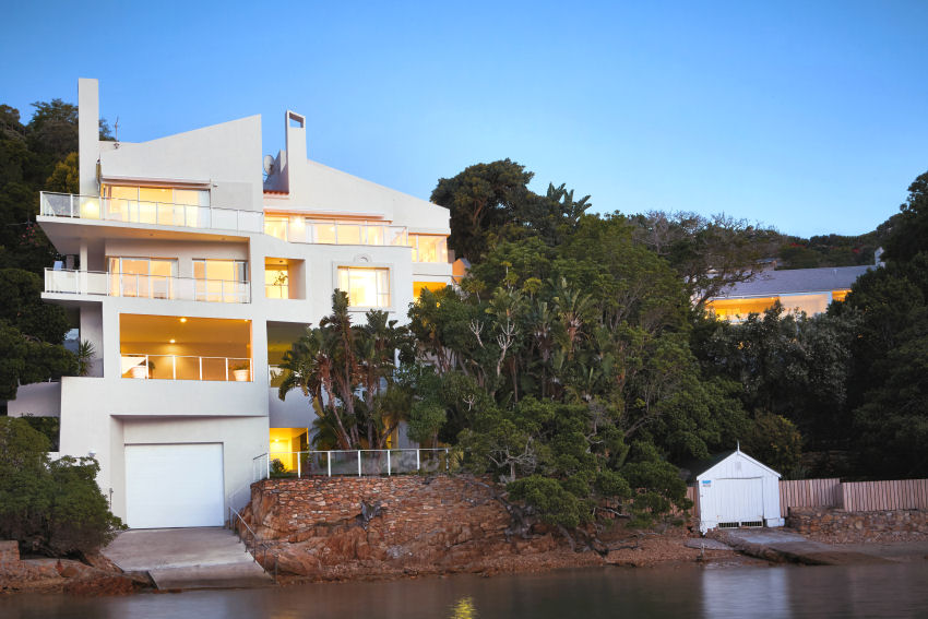 Milkwood Bay: night-time view of house from lagoon